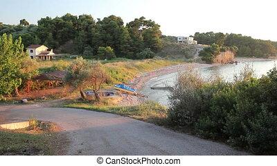 Asphalt going trough green vegetation to the seashore. - Way...