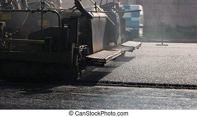 Asphalt paver machine. Cars moving on road. Built to last....