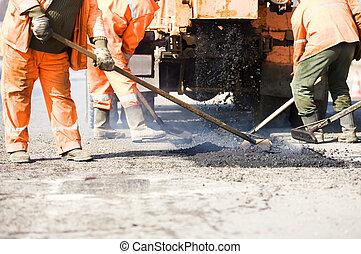 Asphalt paving works - builders at Asphalting paver machine...