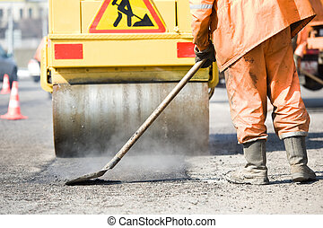 Asphalt paving works with compactor - builder with shovel at...
