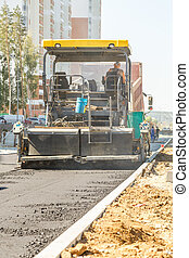 Asphalt-placing machine working on the city road