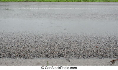 asphalt rainfall water - car automobile pass asphalt road in...
