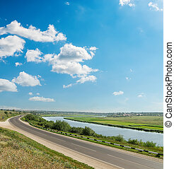 asphalt road and river under blue sky with clouds