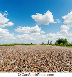asphalt road closeup under clouds in sky