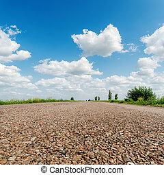 asphalt road closeup under clouds in sky