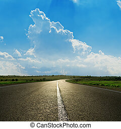 asphalt road closeup under cloudy blue sky