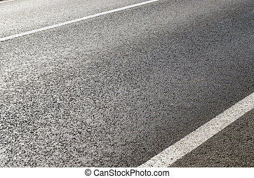 asphalt road closeup with white lines