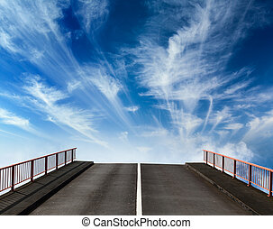Asphalt road going into sky with clouds