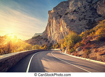 Asphalt road in autumn forest at sunrise. Crimean mountains