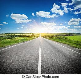 Asphalt road in field under blue sky