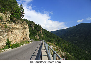 Asphalt road in mountains against the blue sky with white clouds