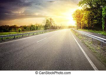 Asphalt road leaving for turn to the sun