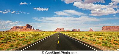 Asphalt road, red sandstone mountains with slyline