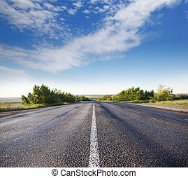 asphalt road through the green field and clouds on blue sky...