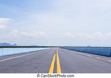 Asphalt road through on blue sky