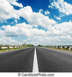 asphalt road to horizon and clouds in blue sky