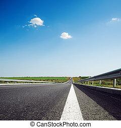 asphalt road to horizon in blue sky