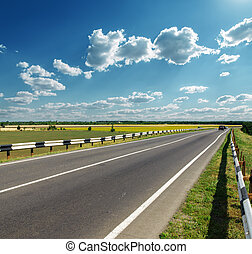 asphalt road to horizon in cloudy sky