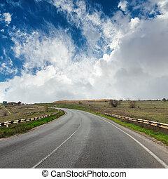asphalt road to horizon in dramatic sky