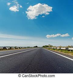 asphalt road to horizon under blue cloudy sky