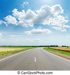 asphalt road under clouds with sun