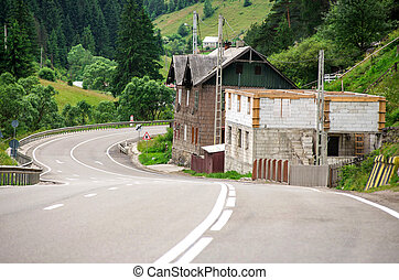 Asphalt road winding through flower hills in Romania