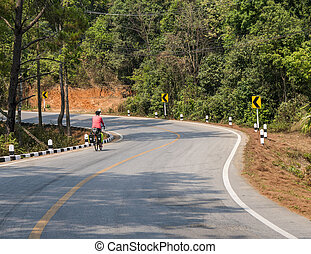 Asphalt road with bicyclist traveler. nature and wildlife views in the middle of the jungle in Thailand National Park.