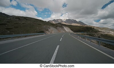 Asphalt road with car passing through forest in region in summer