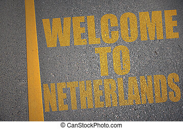 asphalt road with text welcome to netherlands near yellow line.