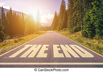 Asphalt road with The End text.