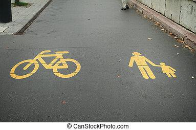 Asphalt road with yellow bike and pedestrian logo