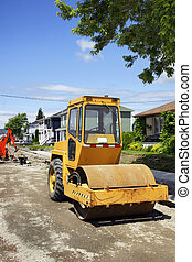 Construction, making pavement on the street of a small town and community neighborood: used yellow asphalt roller on dirt and gravel at the job site with mechanical digger and concrete sidewalk making in the background.