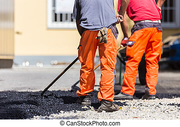 Construction workers during asphalting road works wearing coveralls. Manual labor on construction site.