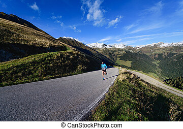 Asphalted mountain road with lonely runner in training