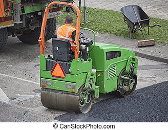 A worker on a mini asphalting machine is fixing road damage caused by winter weather