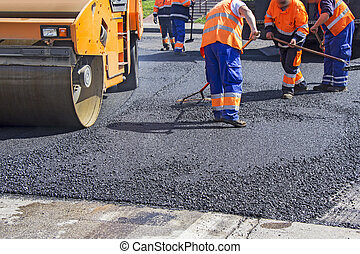 Asphalting city roads - Roller and workers on asphalting and...