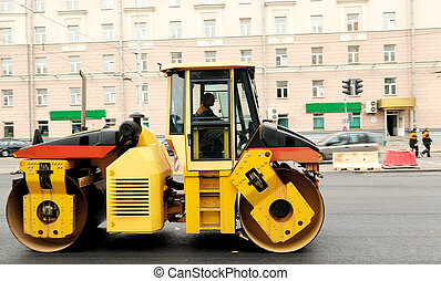 Heavy yellow roller compactor asphalting the town road