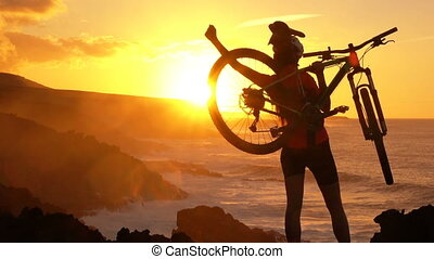 Aspirations. Active lifestyle MTB cyclist mountain biking woman cheering happy raising arms lifting bike by sea during sunset celebrating successful achievement. Person with bicycle in amazing nature.