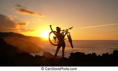 Aspirations, success and achievement. Active lifestyle MTB cyclist mountain biking woman cheering happy raising arms lifting bike by sea at sunset celebrating. Person with bicycle in amazing nature.