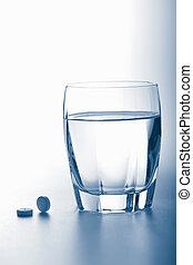 aspirin pills and glass of water toned blue