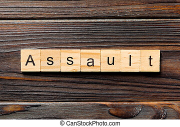 assault word written on wood block. assault text on table, concept