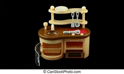 Assemblage of toy kitchen and table with dish. Time lapse.