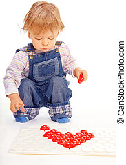 Assemble a mosaic in form of hearts - Kid assemble a mosaic...
