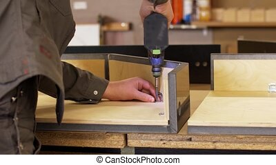 assembler with screwdriver making furniture - production,...