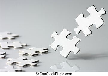 Assembling a jigsaw puzzle. - Close up of two jigsaw puzzle...