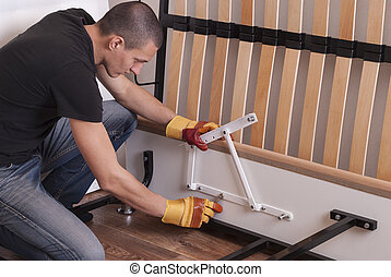 assembling bed furniture - man sets the lifting mechanism on...
