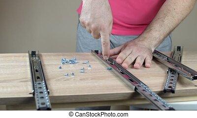 Assembling Drawer Slides - Man installing drawer slides with...