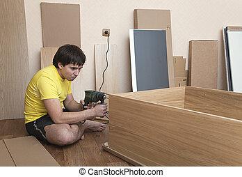Assembling furniture - Young man sitting on floor assembling...