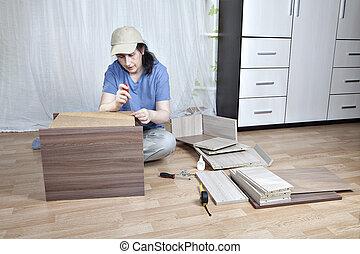 Assembling furniture, woman mounts nightstand screwing hardboard to wooden frame.