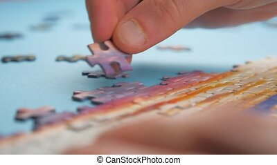 Unfinished jigsaw puzzle. A group of puzzles, hands on blue table background. Puzzle game, preschool education. Puzzle pieces and hands of closeup. Task and subtask concept. Pastime, a hobby